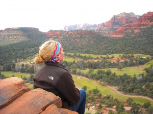 girl up on the red rocks on a sedona retreat overlooking a green sedona valley