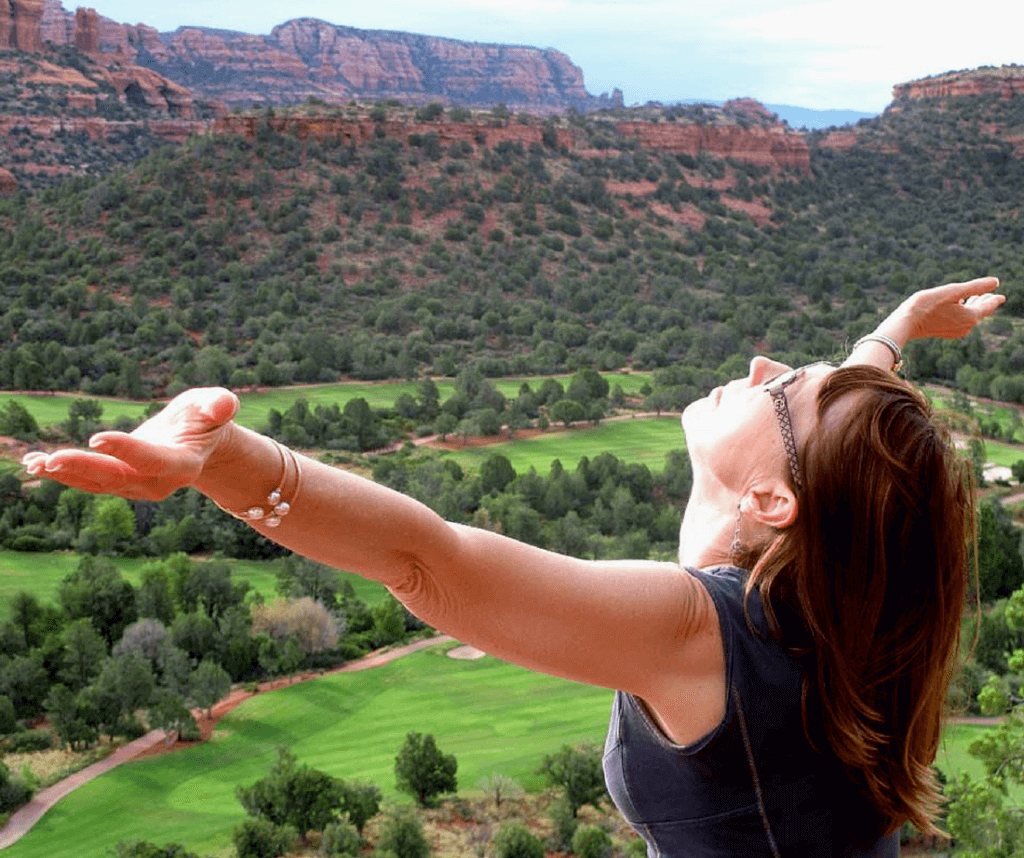 Woman raises her arms to the sun while overlooking the red rocks of Sedona