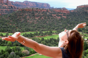 Woman opening her arms to the sky and the red rocks of Sedona