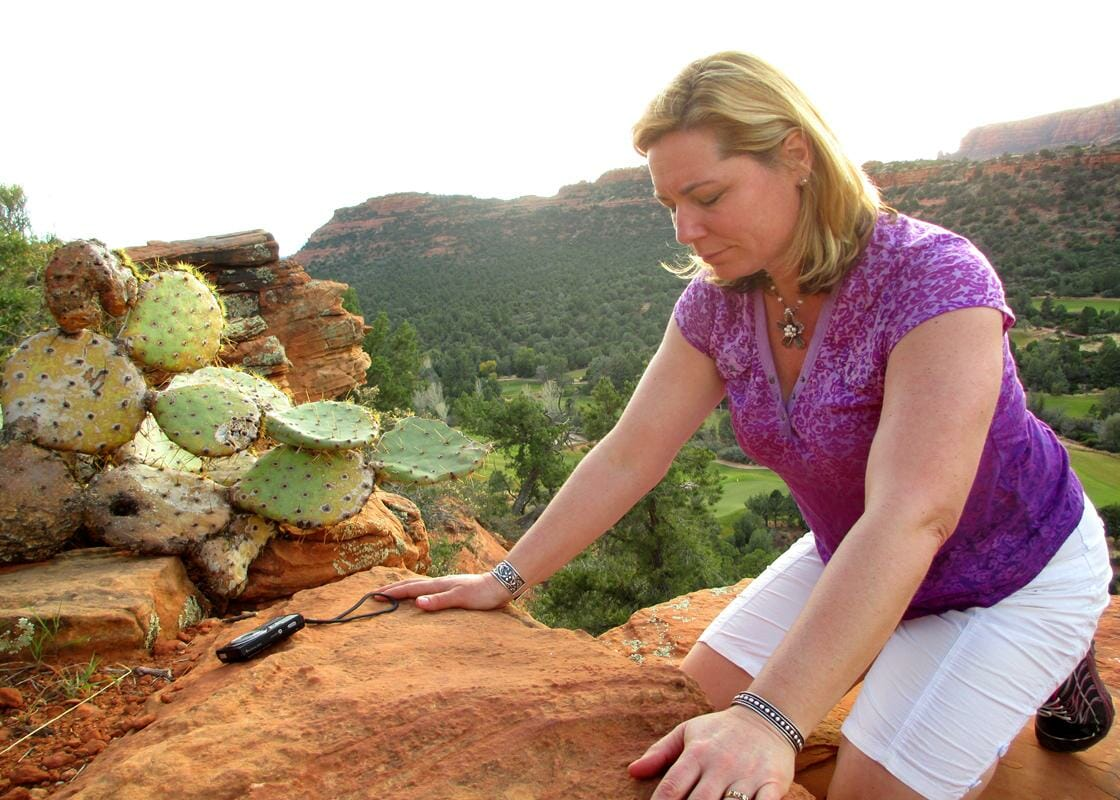 Woman feeling the energy of the red rocks in her hands on a Sedona Vortex Retreat