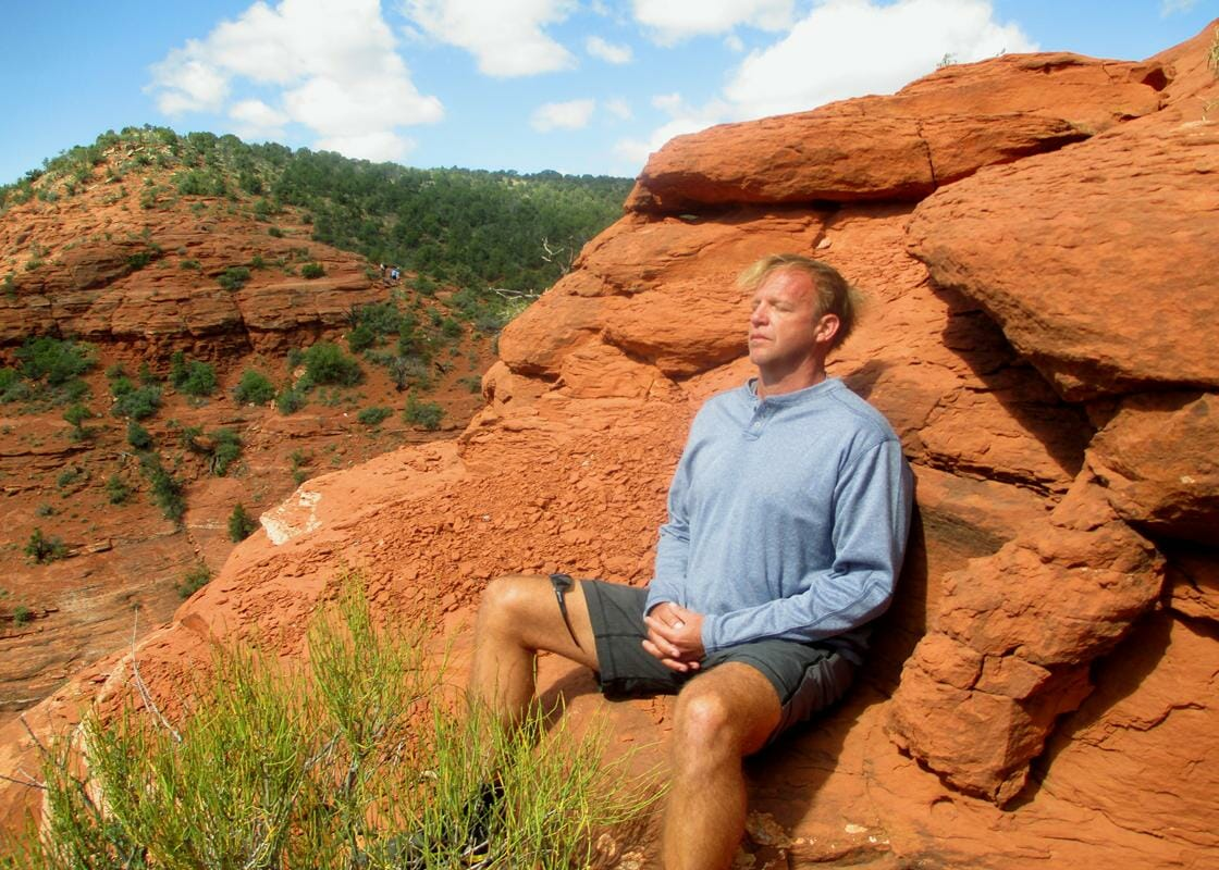Man meditating on the red rocks during a Sedona Vortex Retreat
