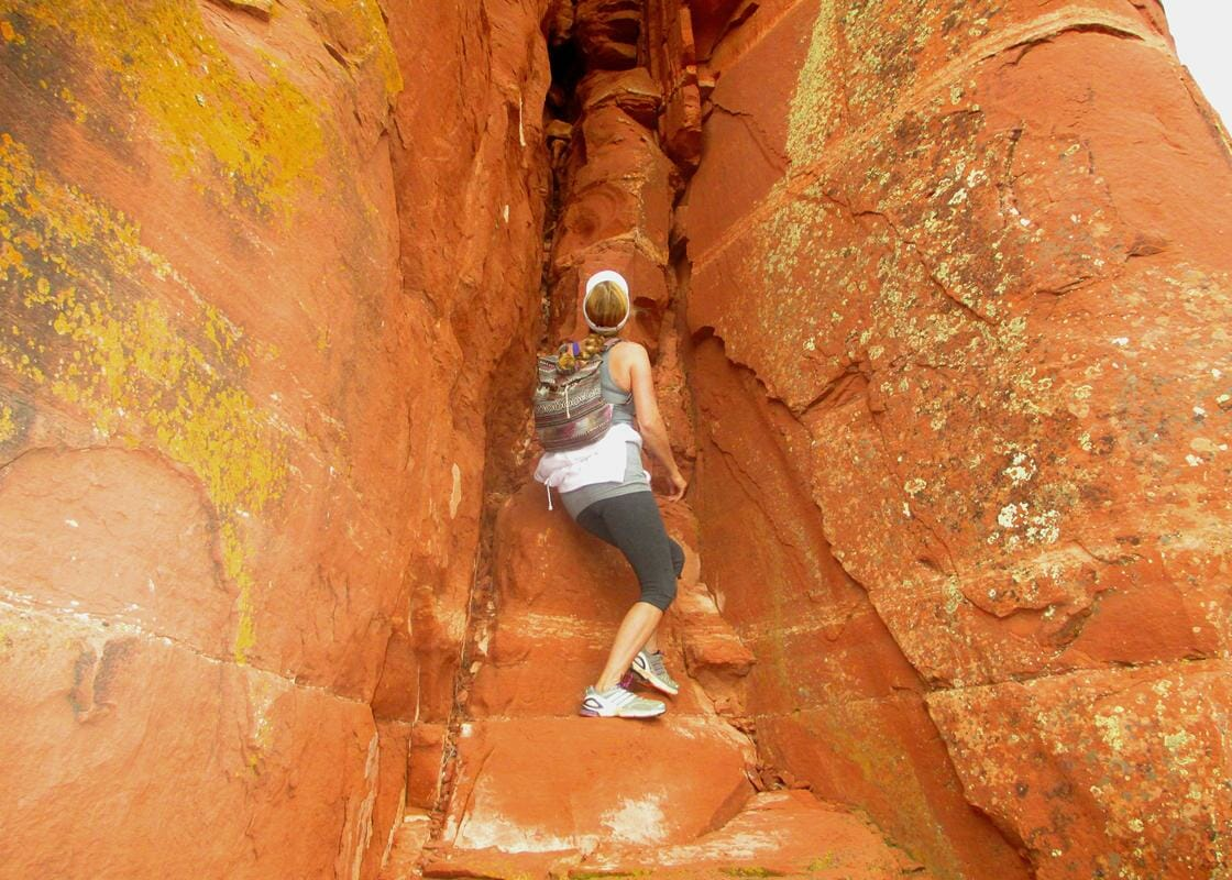 Woman on a Shamanic journey retreat climbs the channel of a red rock