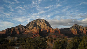 Sedona red rocks reach majestically into a cloudy sky