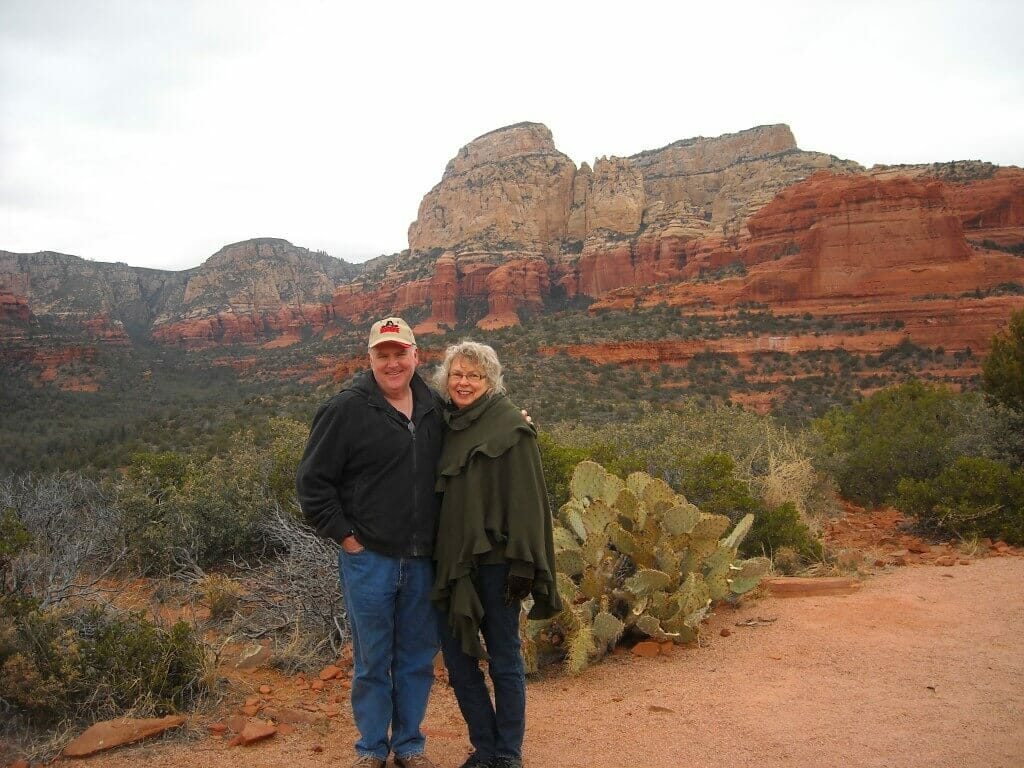 Couple posing in front of red rocks.