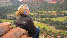 A woman overlooks Verde Valley from the heights of a red rock